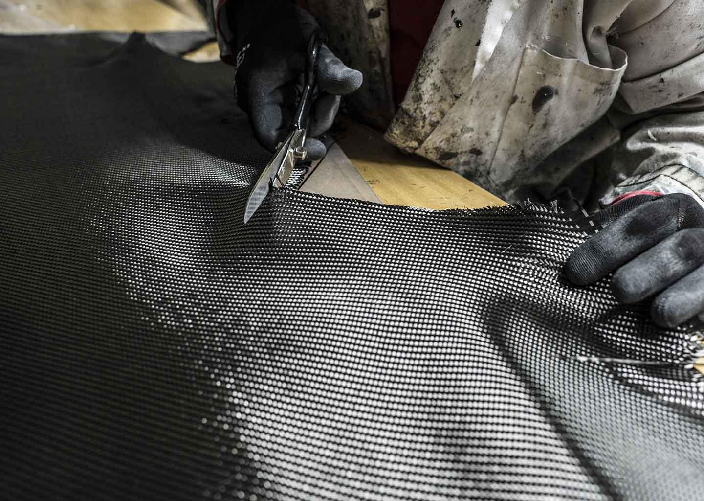 Mann schneidet Kohlefaser zu.