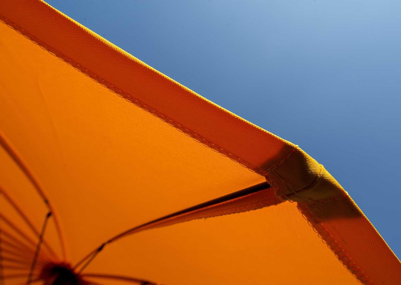 UV-Schutz bei Textilien: Orangener Sonnenschirm vor hellblauem Himmel